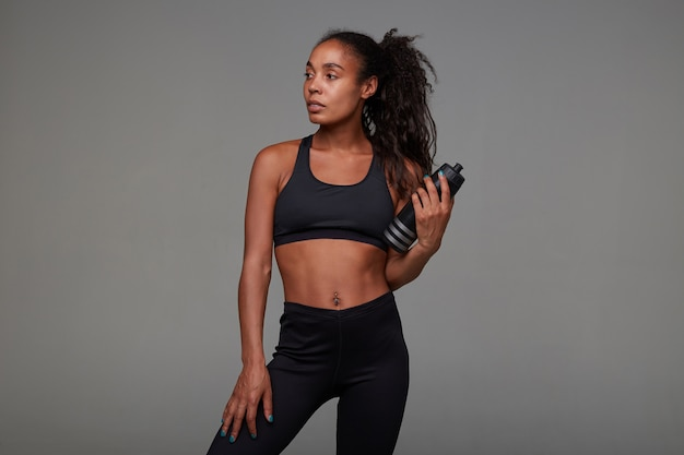 Attractive young dark skinned sportswoman with curly long hair holding fitness bottle in raised hand while standing in black athletic top and leggins