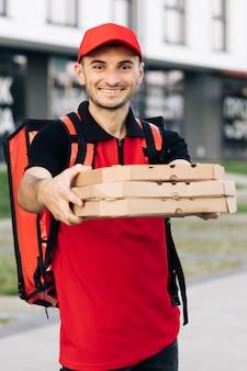 빨간 모자를 쓴 매력적인 젊은 배달원 택배가 피자 상자를 들고 카메라를 향해 웃고 있다