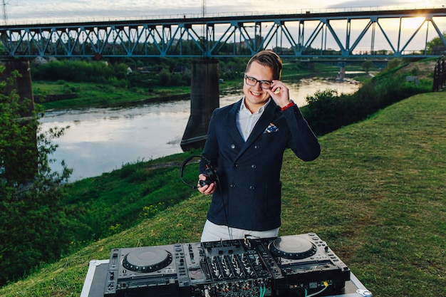 Attractive young dj with headphones and mixer outside in the summertime. bridge, river and sunset on the background