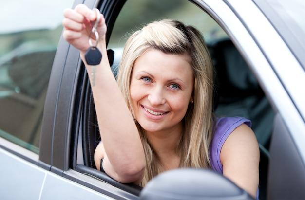 Привлекательный молодой водитель, держащий ключ после того, как новый автомобиль