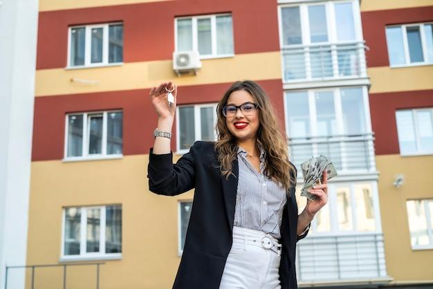 Привлекательный молодой агент по недвижимости, который держит ключи, стоя против нового современного дома на открытом воздухе. концепция продажи
