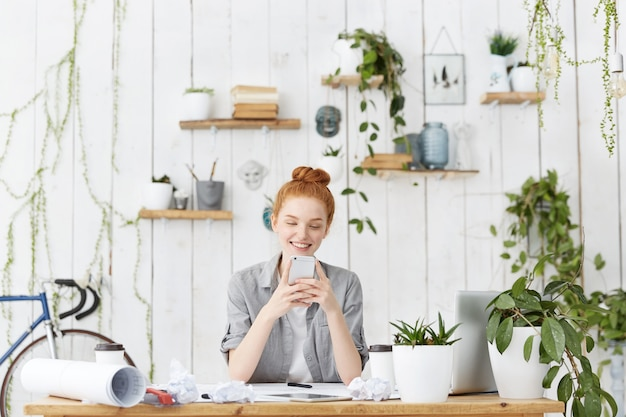 Attractive young european female architect wearing her ginger hair in bun sitting at her workspace
