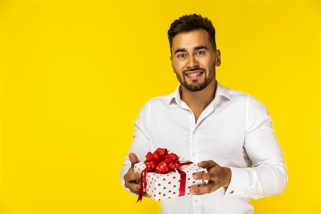 Attractive young european guy in white shirt is holding one present