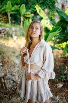 Привлекательная молодая светлокожая женщина стоит возле банановых деревьев в тропическом парке