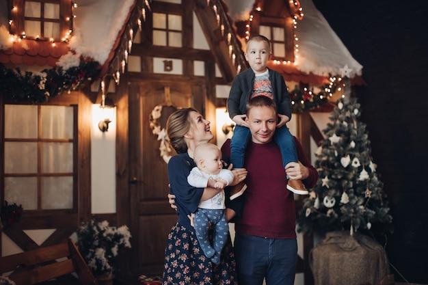 인공 눈으로 장식 된 방에 서있는 두 아들과 함께 매력적인 젊은 가족