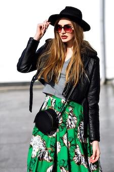 Attraente giovane donna alla moda con i capelli lunghi, in occhiali da sole, cappello nero che guarda al sole, camminando per strada nella mattina di sole. modello elegante, prospettiva di lusso, che esprime emozioni vere