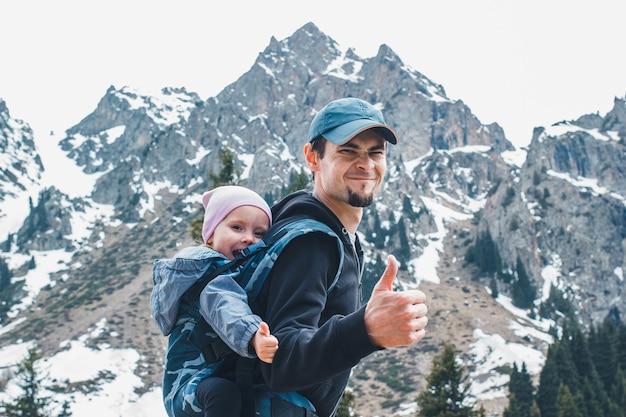 人間工学に基づいたベビーキャリアで赤ちゃんの娘と一緒に山を旅する魅力的な若い父親