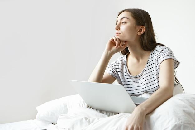 Привлекательная молодая женщина-блогер с темными волосами, работающая над контентом для своего онлайн-блога на ноутбуке, с задумчивым мечтательным взглядом, сидит у белой стены с местом для копирования вашего рекламного контента