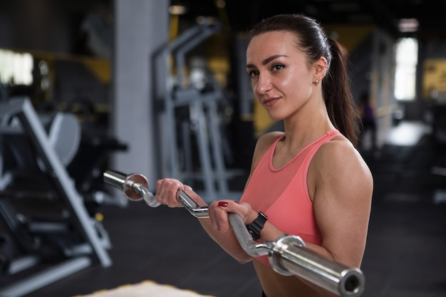 Attractive young female bodybuilder working out with barbell, doing biceps curls at gym