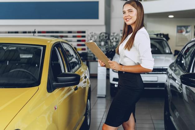 Привлекательная молодая женщина-автодилер стоит в автосалоне возле новой машины