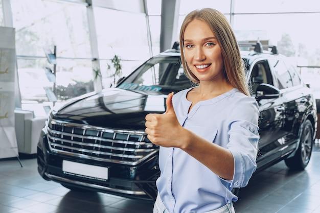Привлекательный молодой женский автомобильный дилер, стоящий в выставочном зале
