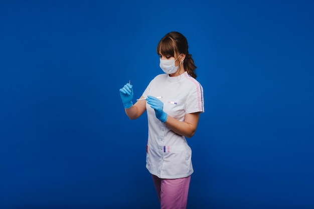 An attractive young female doctor holds a scalpel and looks directly at the camera. concept of healthcare, treatment and surgery. portrait of a medical practitioner on a blue background.