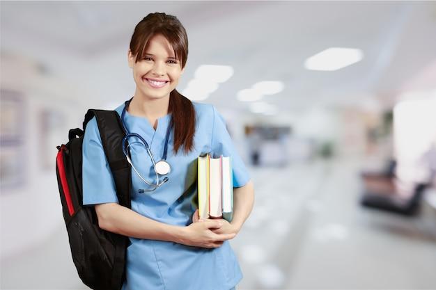 背景にぼやけた病院のインテリアを持つ魅力的な若い女性医師