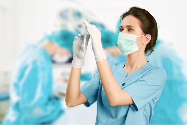背景のぼやけた病院の内部に注射器を持つ魅力的な若い女性医師