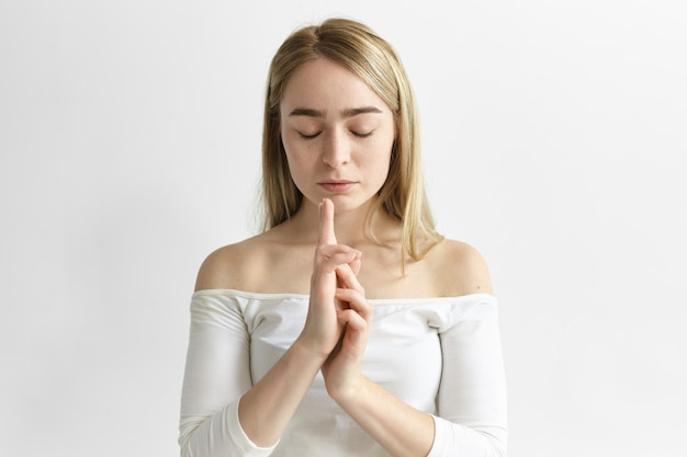 매력적인 젊은 여성 직원이 흰색 사무실에서 명상하고, 눈을 감고 손을 모으고, 자신의 균형을 찾으려고, 호흡 운동을 연습합니다.