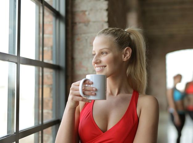 一杯のコーヒーを保持し、窓の外を見ている魅力的な若い女性