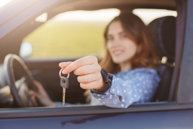 Attractive young female holds car keys, being happy owner of new automobile. lovely woman sells vehicle