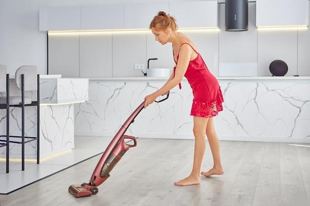 분홍색 잠옷을 입은 매력적인 젊은 여성이 수직 진공 청소기를 사용하여 방을 청소합니다