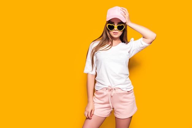 黄色の壁に立っている彼女の帽子に触れるスタイリッシュな衣装で魅力的な若い女性