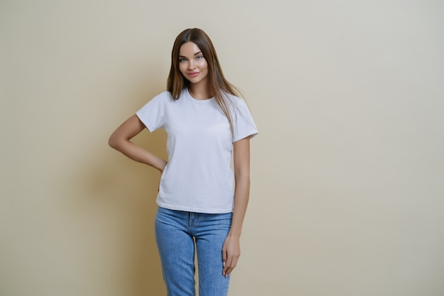 Attractive young female keeps hand on waist, wears casual clothes