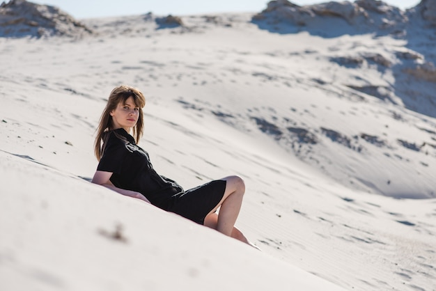 Attractive young female lays at desert dunes