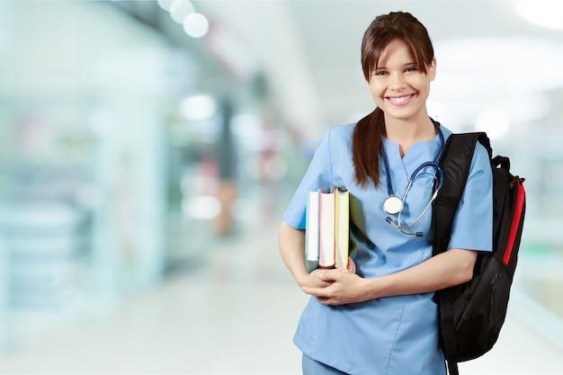 Привлекательная молодая студентка-медик с рюкзаком и книгами
