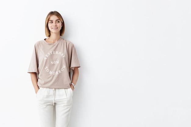 Attraente giovane modella femmina con i capelli raccolti, indossa abiti eleganti, tiene le mani in tasca