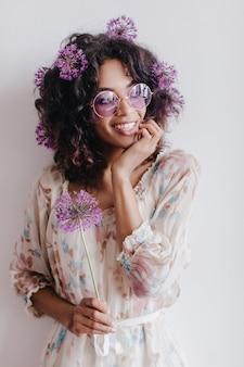 夢のような目をそらしている髪の花を持つ魅力的な若い女性モデル。トレンディなドレスを着た素敵なアフリカの女の子の屋内写真。