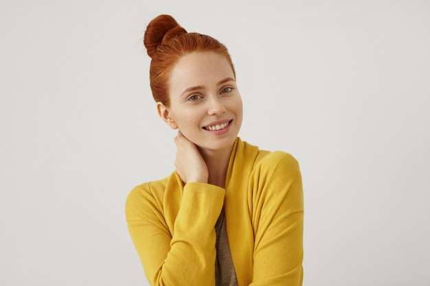Attractive young female model with ginger hair, wearing yellow cape, keeping her hand on neck, looking with happy expression