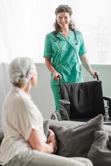 Giovane infermiera femminile attraente che porta sedia a rotelle al paziente senior