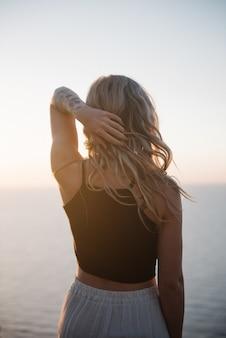 昼間の美しい海のそばの崖の上に立っている魅力的な若い女性