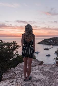 낮 동안 아름다운 바다로 절벽에 서있는 매력적인 젊은 여성