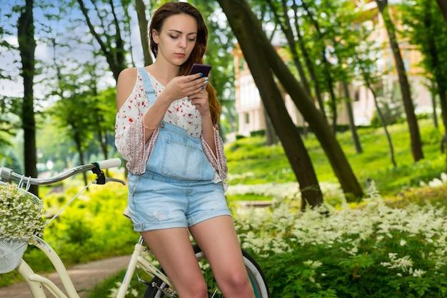 公園のバスケットに小さな白い花の花束を持って自転車に寄りかかってスマートフォンでインターネットサーフィンをしている魅力的な若い女性
