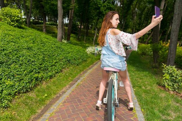 公園で自転車に座ってスマートフォンで自分撮りをしている魅力的な若い女性