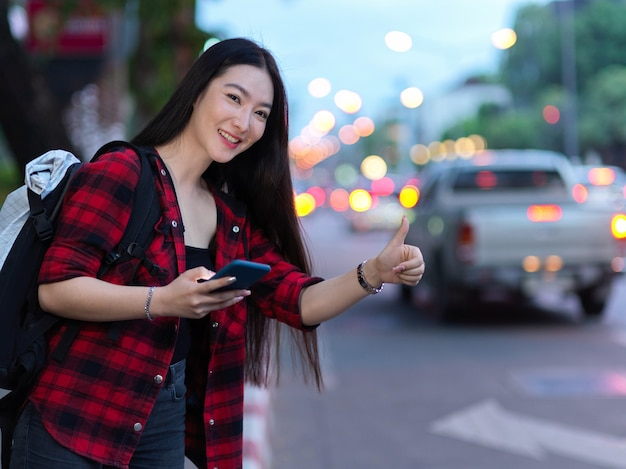 도시 거리의 솔로 여행자에게 택시를 부르기 위해 손으로 사인을 하는 매력적인 젊은 여성 여행자