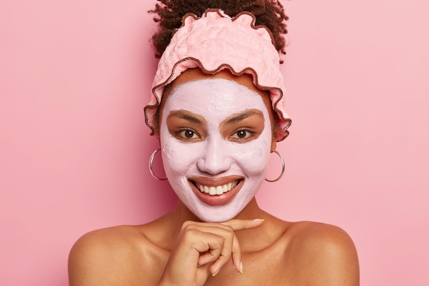 Attractive young female wears bath headband, looks positively into camera, smiles gently, stands naked, poses over pink wall