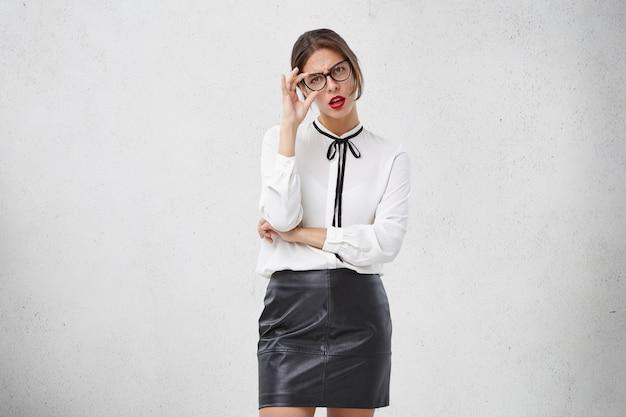 魅力的な若い女性は眼鏡とフォーマルな服を着ています