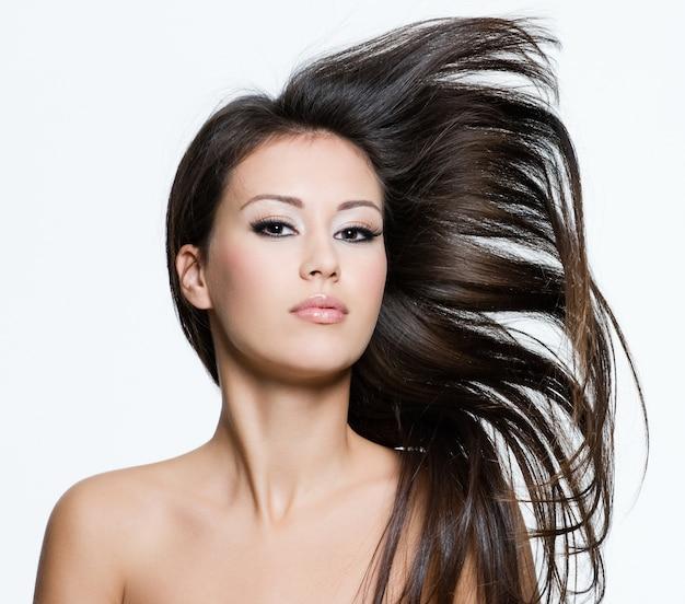 Привлекательная молодая женщина с красивыми длинными каштановыми волосами, позирует изолированной на белом