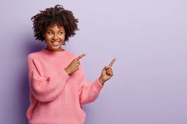 Привлекательная молодая девушка с кудрявыми волосами, зубастой улыбкой, здоровой темной кожей, показывает в сторону на свободное пространство, демонстрирует что-то потрясающее на фоне фиолетовой копии, носит розовый джемпер