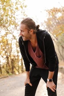 가을 숲에서 조깅하는 매력적인 젊은 스포츠맨, 휴식
