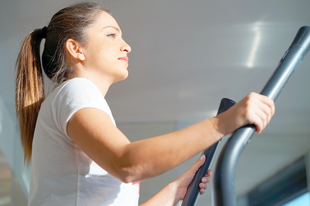Attractive young fitness model runs on a treadmill, is engaged in fitness sport club.