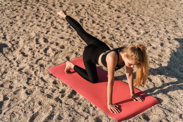 해변에서 매트에 요가 연습을 하 고 매력적인 젊은 피트 니스 여자, 스트레칭