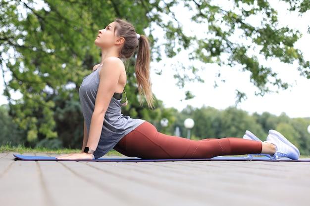 屋外で運動し、ストレッチ運動をする魅力的な若いフィットネス女性。