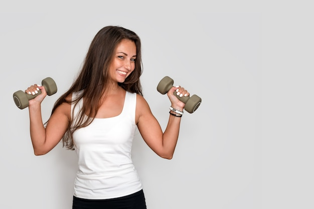 Attractive young fitness woman holding dumbells, athletic girl doing a fitness workout with dumbbells on grey studio background.