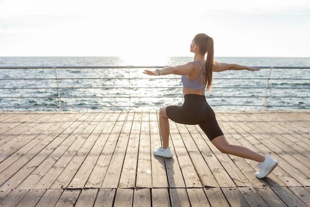 ビーチの日の出でハタヨガの練習を練習している魅力的な若いフィットネス女性