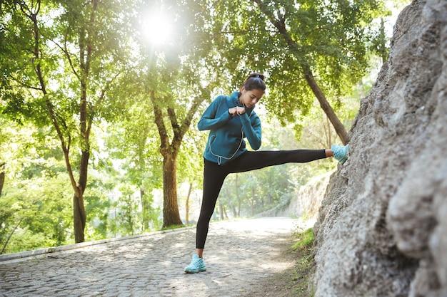 야외에서 운동하는 운동복을 입고 매력적인 젊은 피트 니스 여자, 스트레칭 운동을 하