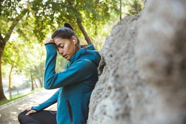 屋外で運動し、トレーニング後に休むスポーツウェアを身に着けている魅力的な若いフィットネス女性