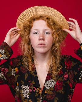 Attractive young ginger woman putting on straw hat