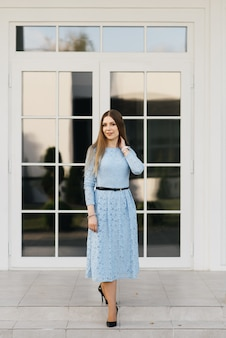Attractive young girl on the background of the white house in a blue dress