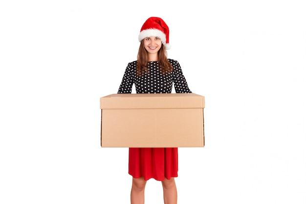 Attractive young girl in christmas hat delivering big cardboard box
